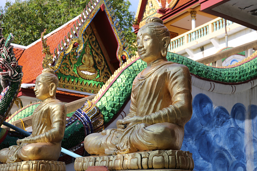 istock Two golden Buddha statues in a temple with a statue of a serpent. 966237548