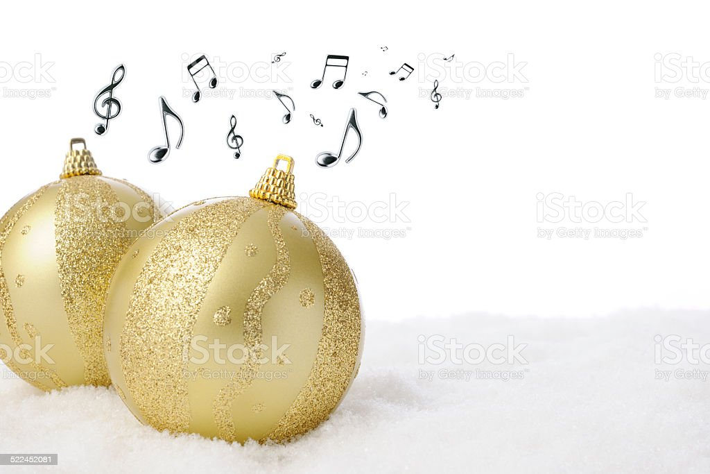 Two golden Christmas balls on the snow with musical note stock photo