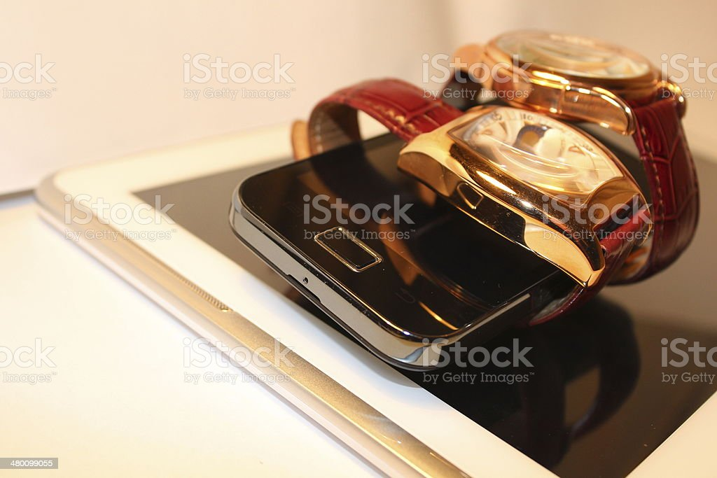 Two golden luxury chronometers around black cell phone (macro) stock photo
