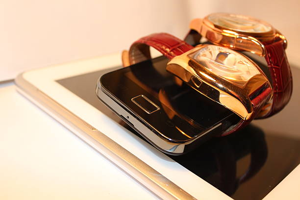 Two golden luxury chronometers around black cell phone (macro) stock photo