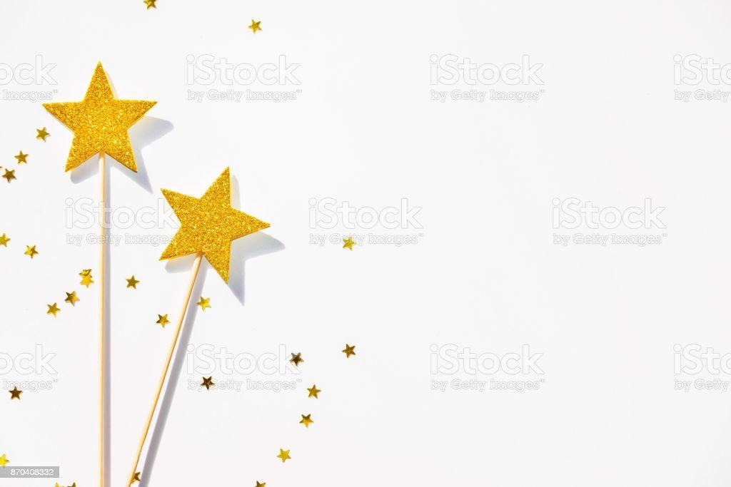 Deux baguettes magiques parti or et paillettes sur un fond blanc. Copiez l'espace. - Photo