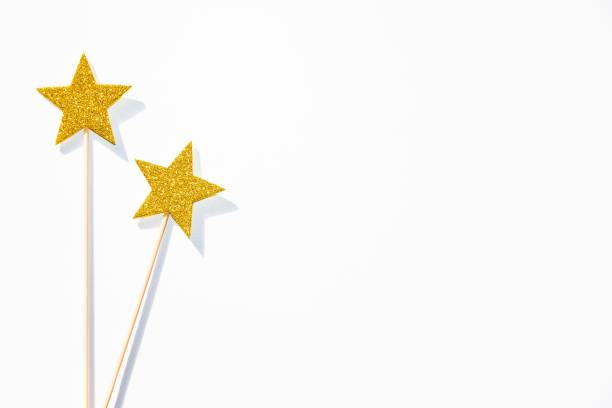 two golden party magic wands on a white background. copy space. - fairy wand stock photos and pictures