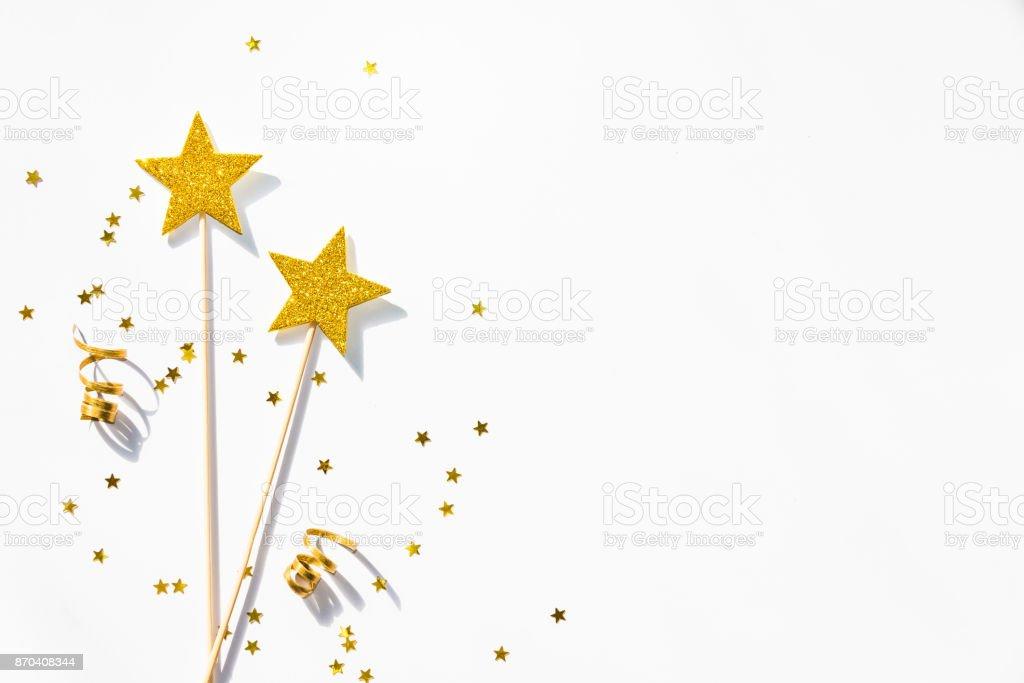 Deux baguettes magiques parti d'or, de paillettes et de rubans sur un fond blanc. Copiez l'espace. - Photo