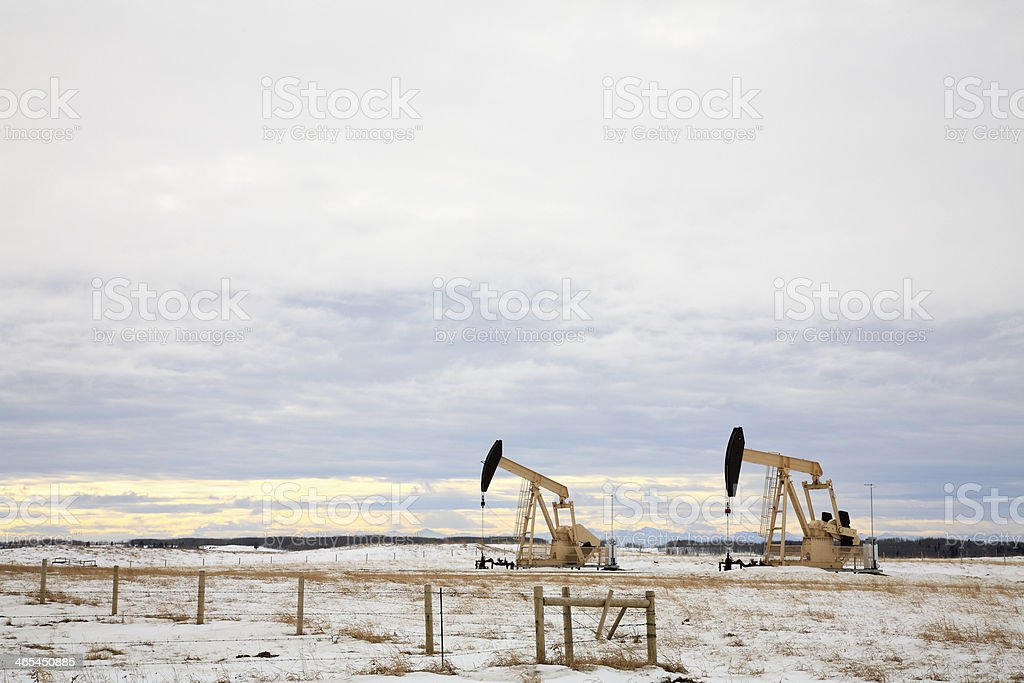 Two Golden Pump Jacks Drilling On Winter Agricultural Land royalty-free stock photo