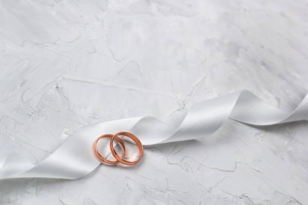 zwei goldene ringe und white satin band hochzeit dekor oder hochzeitseinladung - tischdeko goldene hochzeit stock-fotos und bilder