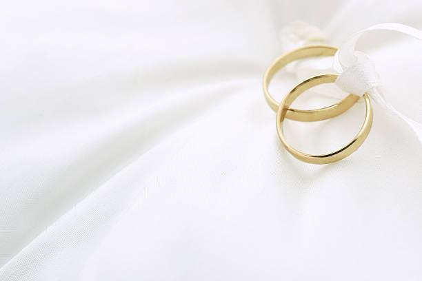 Two golden wedding rings on a satin, white pillow stock photo