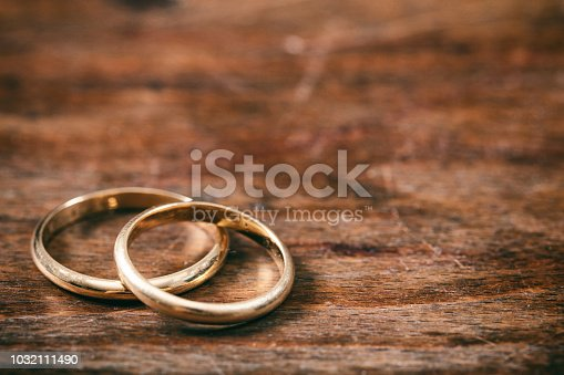A pair of golden wedding rings on wooden background, copy space