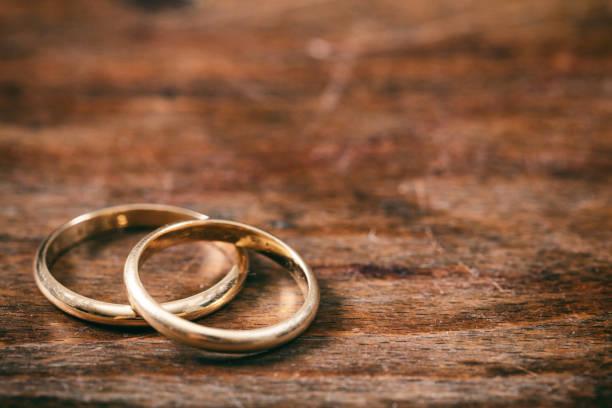 zwei goldene hochzeit ringe auf hölzernen hintergrund, textfreiraum - verlobungsfeier einladungen stock-fotos und bilder