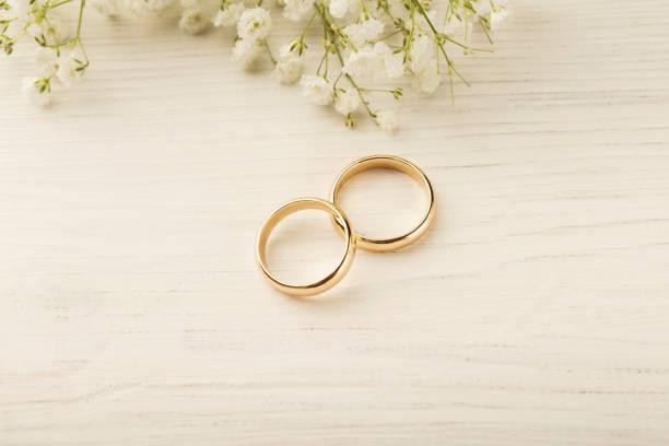zwei goldene hochzeit ringe mit blumenschmuck - heiratsantragsring stock-fotos und bilder