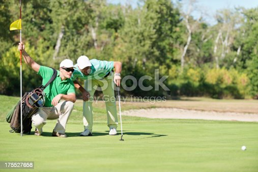 Detail from golf game, contemplating a putting shot