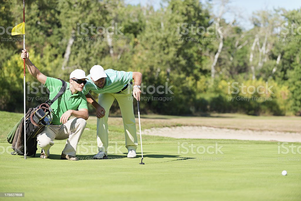 Two golf players staring at the ball stock photo