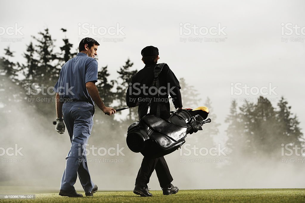 Two golf players walking in golf course, rear view royalty-free stock photo