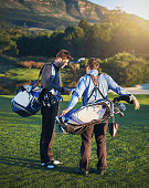Two young male golfers, seen from behind, carrying their bags, discuss something on a beautiful sunlit golf course.