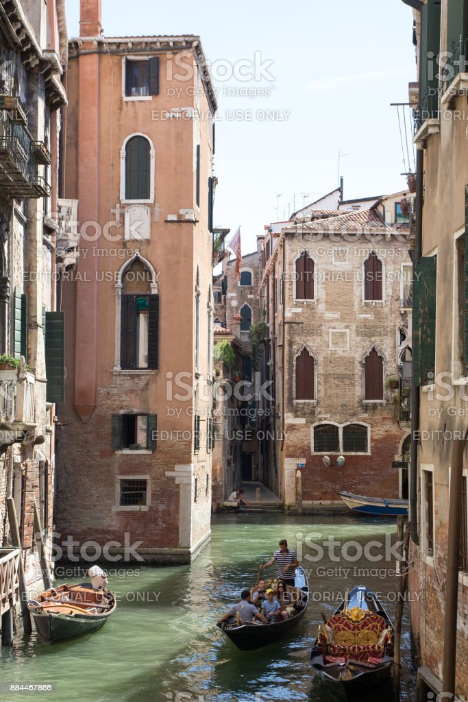 Two gondolas sail through a narrow channel between the houses in Venice stock photo