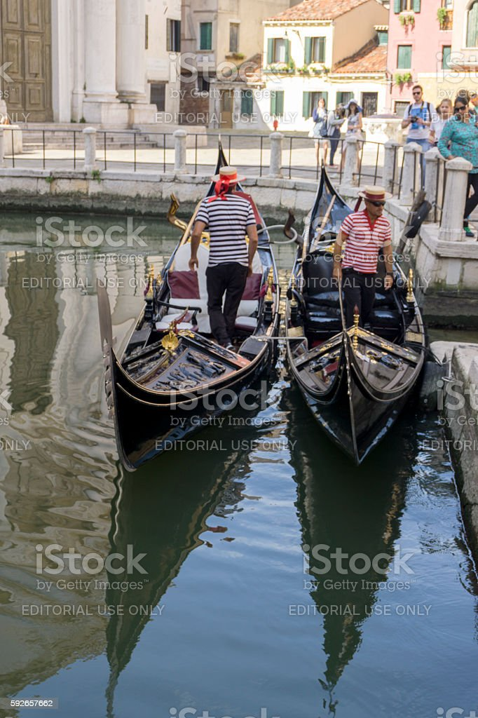 Two Gondolas with Gondoliers moored on a small Venice canal stock photo
