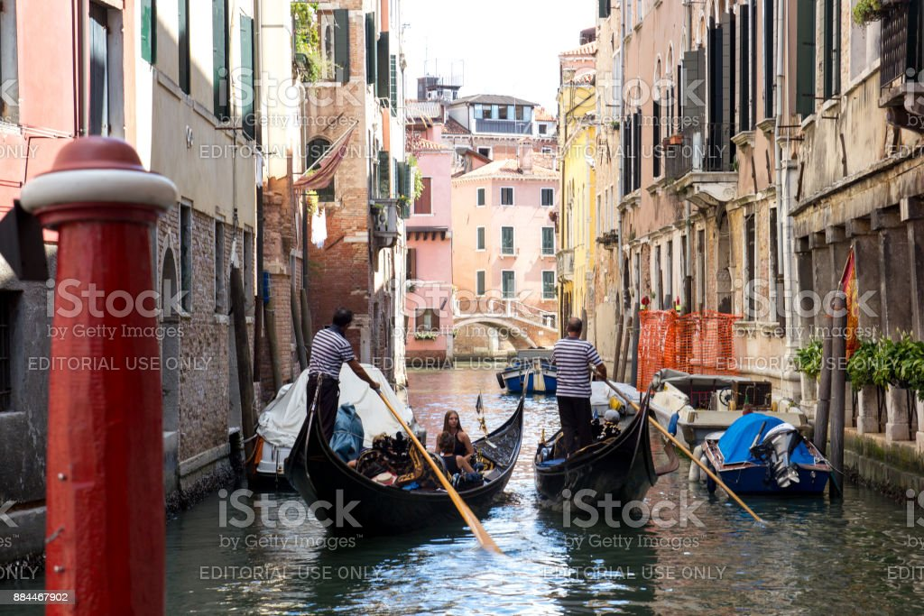Two gondolas with people sail through a narrow channel between the houses in Venice stock photo