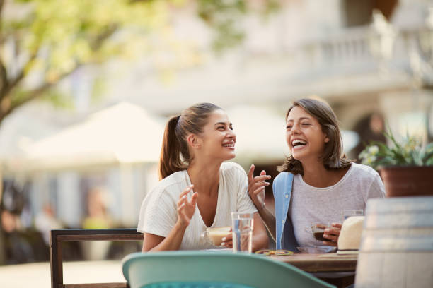 Two gorgeous caucasian friends dressed casual sitting in cafeteria, drinking coffee, chatting and laughing. stock photo