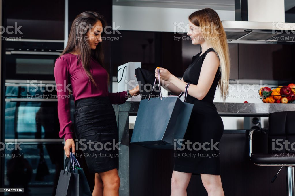 Two gorgeous women after shopping at home. A girl showing her purchases to a female friend standing at home royalty-free stock photo