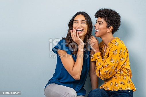 Two best friend girls whispering a secret. Beautiful latin woman and brazilian girl laughing and sharing gossip while sitting against wall with copy space. Stylish friends talking to each other while smiling.