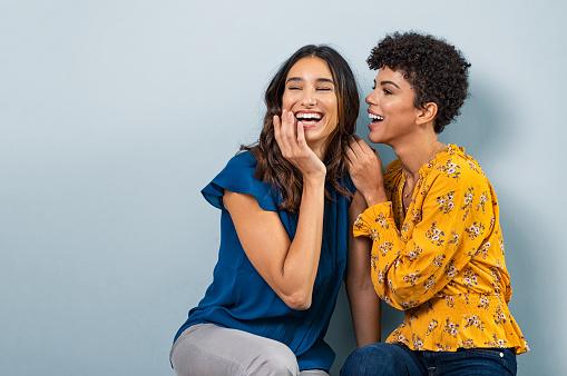 Two gossip women whispering
