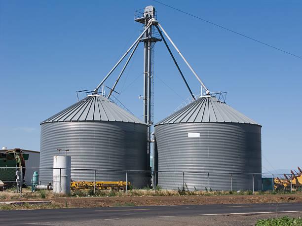 zwei grain silos - maschendrahtzaun preis stock-fotos und bilder