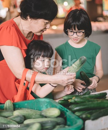 two granddaughters are helping their grandmother selecting cucumber at the retail vegetables stall