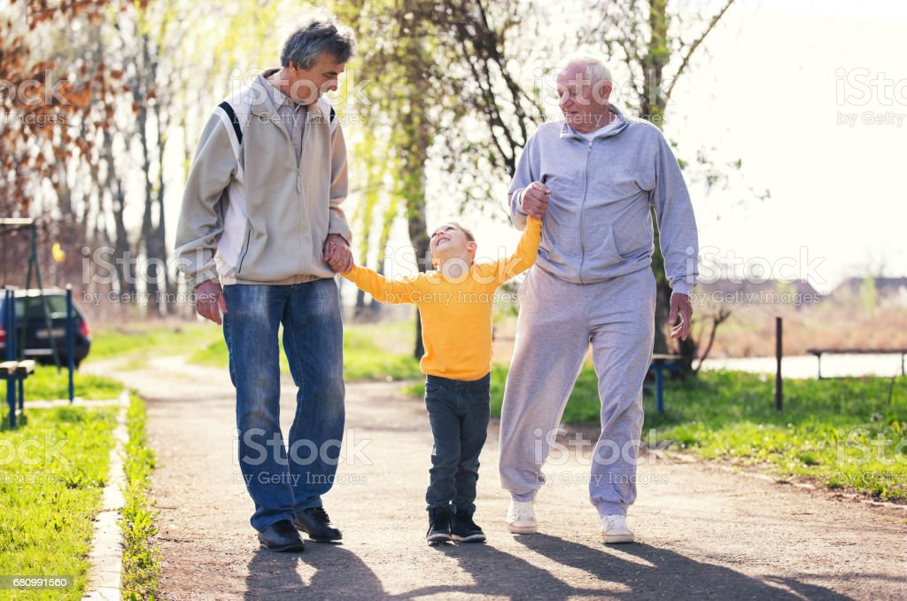 Two grandfather walking with the grandson in the park royalty-free stock photo