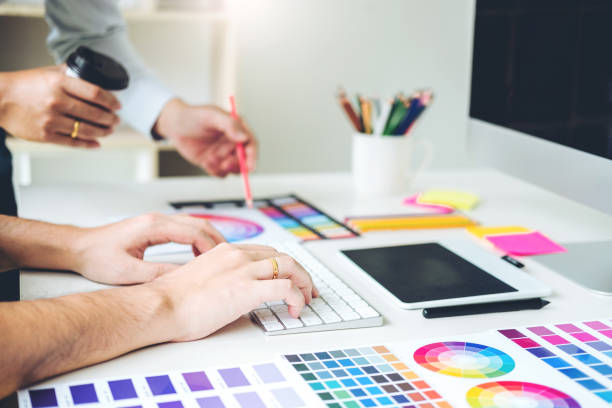 Two Graphic designer drawing on graphics tablet and color palette guide at workplace stock photo