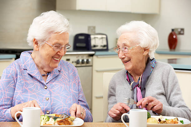 two gray haired friends enjoying a meal together - independence stock photos and pictures
