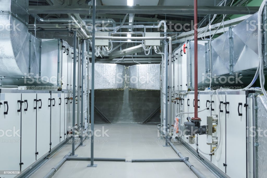 Two gray industrial air handling units in the ventilation plant room with big size ductworks and pipelines stock photo