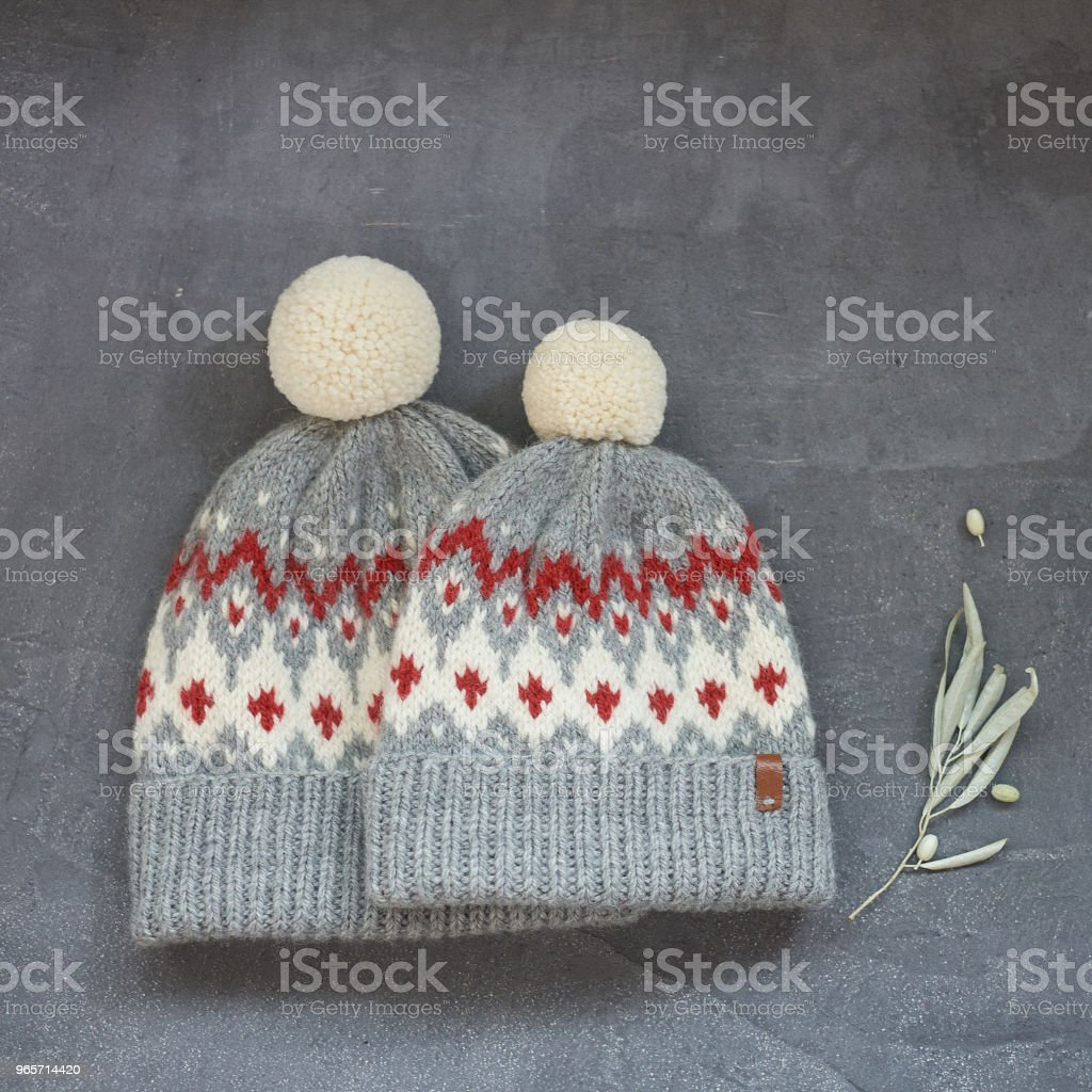 two gray knitted hats with a jacquard pattern on a gray background - Royalty-free Autumn Stock Photo