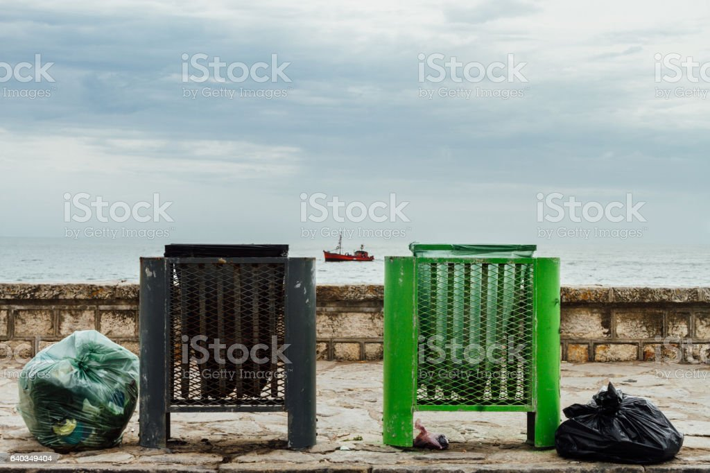 Two green and black garbage baskets with boat stock photo