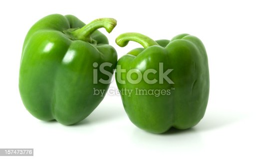 Two green bell peppers isolated on a plain white background, with shadows underneath.
