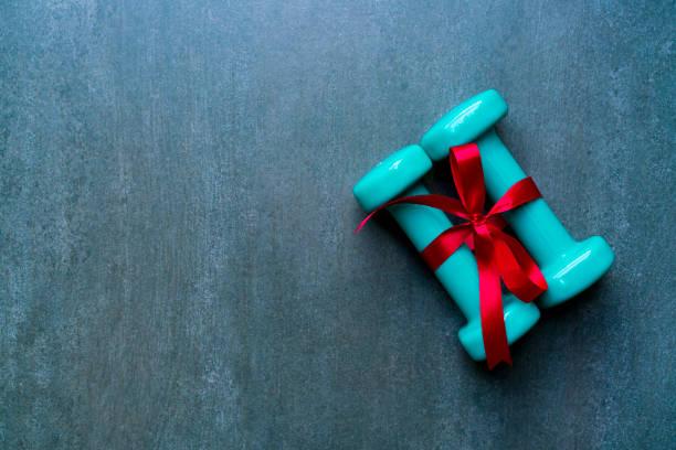 zwei grüne hantel mit roten geschenk-schleife auf einem schwarzen tisch hintergrund, sport und gesunde konzeptionierung - gute geschenke stock-fotos und bilder
