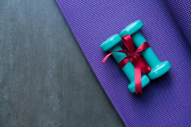 zwei grüne hantel mit roten geschenk bogen auf eine yoga matte hintergrund, sport und gesundes konzept - besondere geschenke stock-fotos und bilder