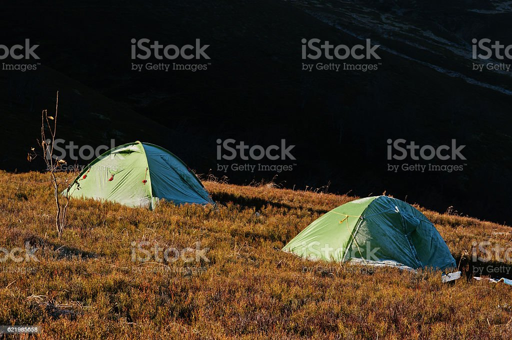 Two green frost camping tent on sunlight of mountains. stock photo