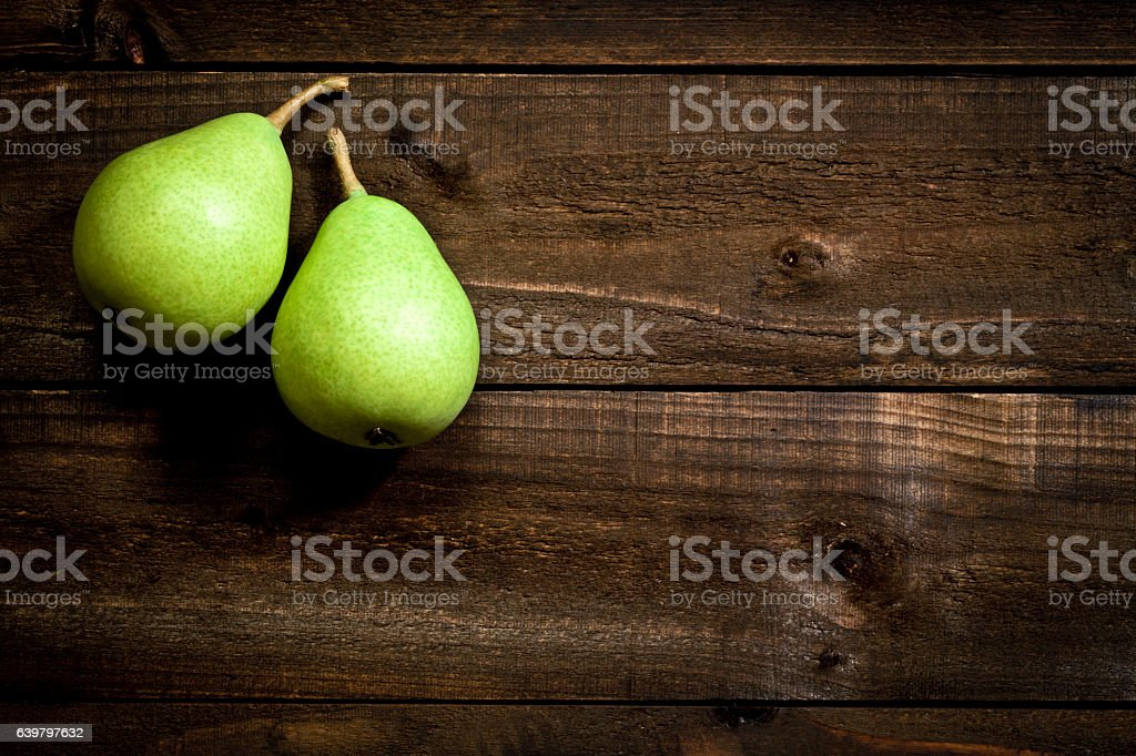 Two green pears on rustic wooden table – Foto