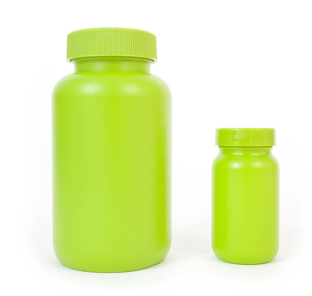 Two Green Plastic Bottles Two green plastic bottles, large and small, side by side, on a white background. generic drug stock pictures, royalty-free photos & images