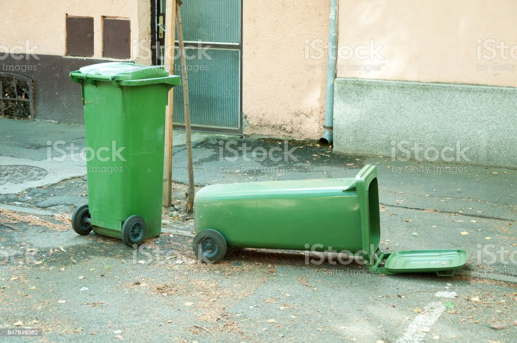 Two green plastic garbage can one is overturned lying on the street stock photo