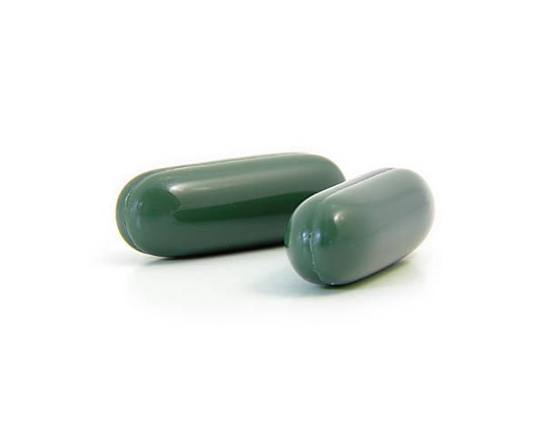 zwei tabletten green tea - grüner tee kapseln stock-fotos und bilder
