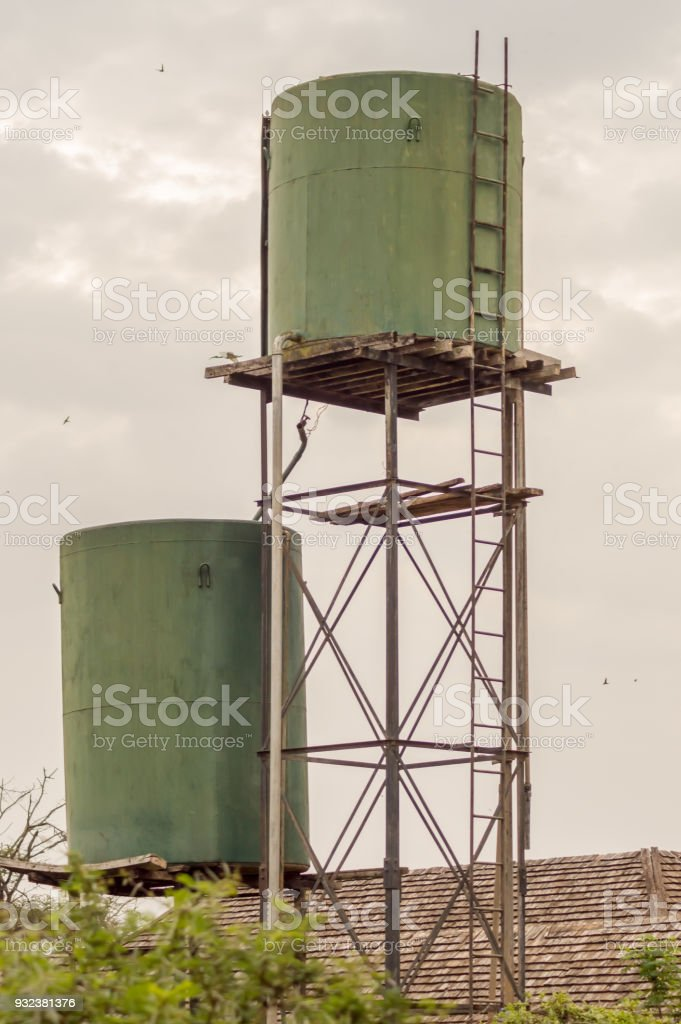 Two green water storage tanks on stilts in the savannah of Amboseli Park in Kenya stock photo