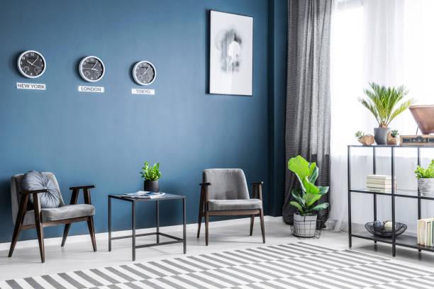 zwei graue sessel, metallständer mit dekor, fenster mit vorhängen und frischen pflanzen platziert im dunklen wohnzimmer interieur - uhrenhalter stock-fotos und bilder