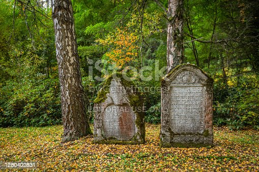 Marianske Lazne, Czech Republic - October 12 2020: Tombstones covered with moss standing at Jewish cemetery. Yellow, green and orange leaves on ground and trees.
