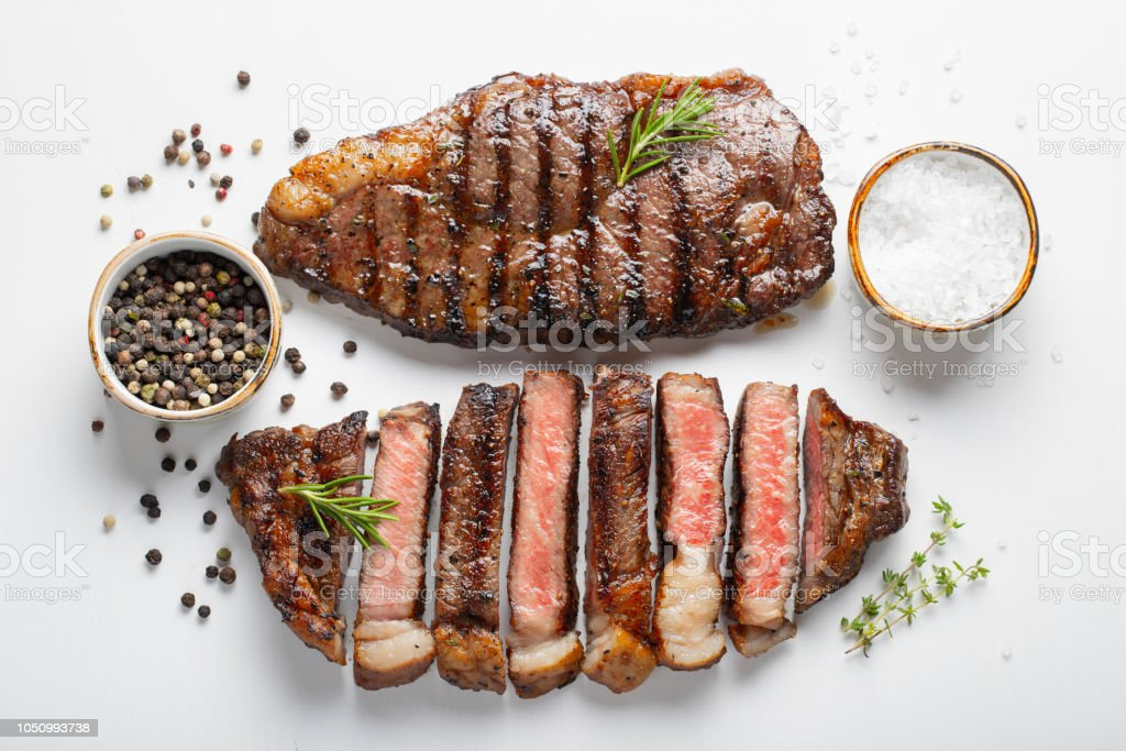 Two grilled marbled beef steaks striploin with spices isolated on white background, top view stock photo
