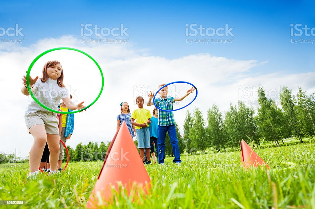 Two group of kids playing with hula hoops stock photo