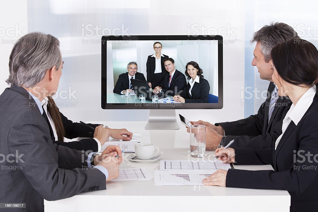 Two groups of businesspeople conversing via video conference stock photo