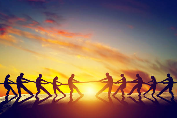 Two groups of people pulling line, playing tug of war. stock photo