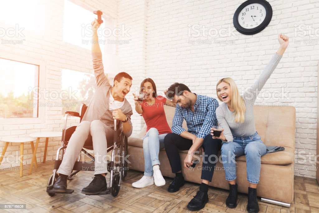 Two guys and two girls play on the game console. stock photo