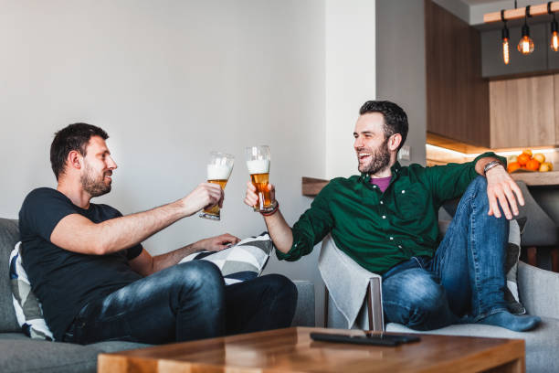 Two guys drinking beer and having fun in the living room stock photo