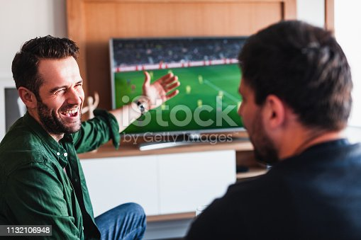 Two guys drinking beer watching football